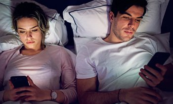 couple-viewing-smartphones-in-bed-350